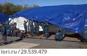 Купить «Group of rescuers setting up an army field tent, deploy campground on windy day», видеоролик № 29539479, снято 2 октября 2018 г. (c) А. А. Пирагис / Фотобанк Лори