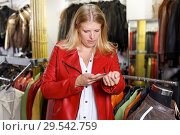 Купить «Woman trying on leather jacket», фото № 29542759, снято 5 сентября 2018 г. (c) Яков Филимонов / Фотобанк Лори