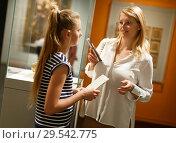 Купить «Girl with mother talking near art exhibition in museum, using guidebook», фото № 29542775, снято 21 октября 2018 г. (c) Яков Филимонов / Фотобанк Лори