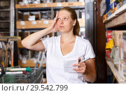 Купить «Female holding shop list and choosing tools at shelves in build store», фото № 29542799, снято 20 сентября 2018 г. (c) Яков Филимонов / Фотобанк Лори