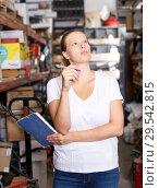 Купить «Young woman standing near racks in build store bebore buying tools», фото № 29542815, снято 20 сентября 2018 г. (c) Яков Филимонов / Фотобанк Лори