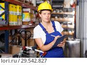 Купить «Young woman customer in helmet with notebook looking construction materials», фото № 29542827, снято 20 сентября 2018 г. (c) Яков Филимонов / Фотобанк Лори