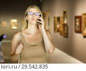 Купить «Woman talking on phone in art museum», фото № 29542835, снято 22 сентября 2018 г. (c) Яков Филимонов / Фотобанк Лори