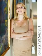 Купить «Woman wearing glasses looking at pictures», фото № 29542851, снято 22 сентября 2018 г. (c) Яков Филимонов / Фотобанк Лори