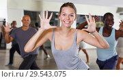 Купить «Group of active young woman and men practicing modern dance together», фото № 29543075, снято 30 июля 2018 г. (c) Яков Филимонов / Фотобанк Лори