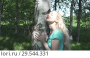 Купить «The young woman with a long fair hair embraces and strokes a white trunk of a birch in summer sunny day», видеоролик № 29544331, снято 20 сентября 2008 г. (c) Вознесенская Ольга / Фотобанк Лори
