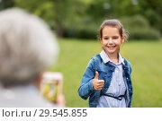 Купить «girl being photographed and showing thumbs up», фото № 29545855, снято 11 августа 2018 г. (c) Syda Productions / Фотобанк Лори