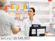 apothecary selling drug to senior man at pharmacy. Стоковое фото, фотограф Syda Productions / Фотобанк Лори