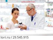 Купить «apothecary and woman with drug at pharmacy», фото № 29545915, снято 27 июня 2015 г. (c) Syda Productions / Фотобанк Лори