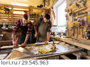 carpenters working with wooden board at workshop. Стоковое фото, фотограф Syda Productions / Фотобанк Лори