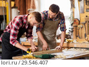 carpenters with ruler and wooden board at workshop. Стоковое фото, фотограф Syda Productions / Фотобанк Лори