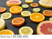 Купить «close up of different citrus fruit slices», фото № 29546435, снято 4 апреля 2018 г. (c) Syda Productions / Фотобанк Лори