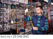 attentive male choosing fishing rod for fishing in the sports shop. Стоковое фото, фотограф Яков Филимонов / Фотобанк Лори