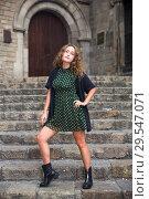 Купить «Young woman tourist in dress standing at stone stair and playfully posing», фото № 29547071, снято 24 сентября 2018 г. (c) Яков Филимонов / Фотобанк Лори