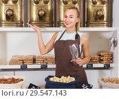 Купить «Young woman is standing on her workplace», фото № 29547143, снято 4 сентября 2017 г. (c) Яков Филимонов / Фотобанк Лори