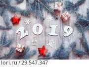 Купить «New Year 2019 background,2019 figures,Christmas toys, blue fir tree branches and snowflakes.New Year 2019 holiday design», фото № 29547347, снято 29 ноября 2016 г. (c) Зезелина Марина / Фотобанк Лори