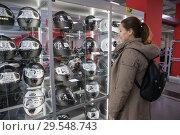 Женщина выбирает мотоциклетный шлем в магазине мотоэкипировки (2018 год). Редакционное фото, фотограф Кекяляйнен Андрей / Фотобанк Лори