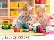 Купить «Preschool boy and girl playing on floor with educational toys. Children at home or daycare.», фото № 29553371, снято 14 декабря 2018 г. (c) Оксана Кузьмина / Фотобанк Лори