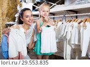 Купить «Woman with small girl choosing white baby clothes», фото № 29553835, снято 20 июля 2019 г. (c) Яков Филимонов / Фотобанк Лори
