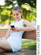 Купить «girl sitting on a bench and using mobile in garden», фото № 29554099, снято 8 июня 2017 г. (c) Яков Филимонов / Фотобанк Лори