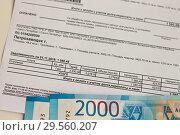 Купить «На столе лежит квитанция за отопление,на ней две купюры по 2 тыс.руб», фото № 29560207, снято 12 марта 2019 г. (c) Людмила Капусткина / Фотобанк Лори