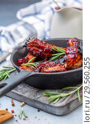 Купить «Cast iron pan with baked pork ribs and fresh rosemary», фото № 29560255, снято 9 декабря 2018 г. (c) Марина Сапрунова / Фотобанк Лори