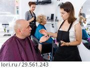 Купить «Hairdresser discussing with male customer», фото № 29561243, снято 26 июня 2018 г. (c) Яков Филимонов / Фотобанк Лори