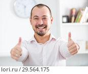 Купить «Positive young man in office», фото № 29564175, снято 23 марта 2019 г. (c) Яков Филимонов / Фотобанк Лори