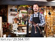 Купить «man worker displaying various belts in leather workshop», фото № 29564191, снято 19 января 2019 г. (c) Яков Филимонов / Фотобанк Лори