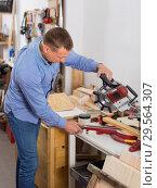 Купить «Woodworker male cutting wooden plank with fret saw in workplace», фото № 29564307, снято 17 мая 2017 г. (c) Яков Филимонов / Фотобанк Лори