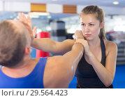 Купить «Happy woman is fighting with trainer», фото № 29564423, снято 21 августа 2017 г. (c) Яков Филимонов / Фотобанк Лори