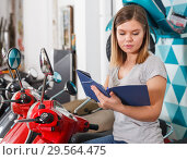 Купить «Woman is shopping and choosing new motobike», фото № 29564475, снято 8 мая 2018 г. (c) Яков Филимонов / Фотобанк Лори
