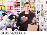 Купить «Female is standing in needlework store», фото № 29564615, снято 10 мая 2017 г. (c) Яков Филимонов / Фотобанк Лори