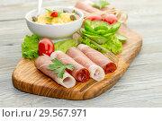 Купить «Pieces of Italian prosciutto on a wooden cutting board», фото № 29567971, снято 12 декабря 2018 г. (c) Татьяна Ляпи / Фотобанк Лори