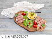 Купить «Pieces of Italian prosciutto on a wooden cutting board», фото № 29568007, снято 12 декабря 2018 г. (c) Татьяна Ляпи / Фотобанк Лори