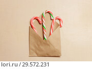 Top view three candy canes in brown envelope on brown color wood background. Стоковое фото, фотограф Максим Бейков / Фотобанк Лори