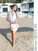 Купить «Attractive girl in swimsuit with hat standing near hotel at ocean shore», фото № 29573151, снято 10 июля 2018 г. (c) Яков Филимонов / Фотобанк Лори