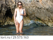 Купить «Sexy woman in swimsuit and sunglasses near stones at sea shore», фото № 29573163, снято 10 июля 2018 г. (c) Яков Филимонов / Фотобанк Лори