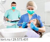 Купить «Female dentist performing treatment for girl with assistant», фото № 29573431, снято 1 марта 2018 г. (c) Яков Филимонов / Фотобанк Лори