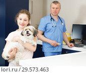 Купить «Smiling girl with puppy visiting veterinarian clinic», фото № 29573463, снято 3 мая 2018 г. (c) Яков Филимонов / Фотобанк Лори