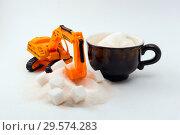 Купить «Toy excavator loads cube sugar into a real cup of coffee on a light background», фото № 29574283, снято 13 декабря 2018 г. (c) Евгений Харитонов / Фотобанк Лори