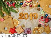 Купить «Рождественский фон с пряниками. Новогодние игрушки ,печенье и конфеты на бумаге. Надпись 2019.», фото № 29574375, снято 16 декабря 2018 г. (c) ирина реброва / Фотобанк Лори