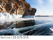 Купить «Lake Baikal. Olkhon Island in the winter. Beautiful smooth transparent ice with cracks near the rocks with the icy grotto on a sunny frosty day», фото № 29575515, снято 8 марта 2015 г. (c) Виктория Катьянова / Фотобанк Лори