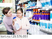 Купить «Woman with girl looking for cleaners in supermarket», фото № 29576051, снято 5 января 2017 г. (c) Яков Филимонов / Фотобанк Лори