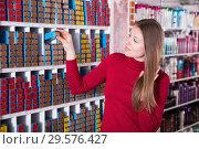 Купить «Young woman customer is choosing colored hair dye in shop», фото № 29576427, снято 22 марта 2018 г. (c) Яков Филимонов / Фотобанк Лори