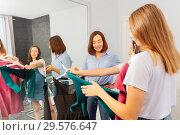 Купить «Mom helping daughters to choose going out outfit», фото № 29576647, снято 7 июля 2018 г. (c) Сергей Новиков / Фотобанк Лори