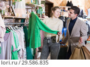 Купить «Young female with male are looking on green jacket for her», фото № 29586835, снято 12 марта 2018 г. (c) Яков Филимонов / Фотобанк Лори