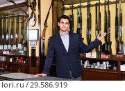 Handsome adult male owner of hunting shop offering rifle. Стоковое фото, фотограф Яков Филимонов / Фотобанк Лори