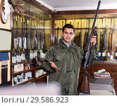 Young male hunter choosing shotgun in store. Стоковое фото, фотограф Яков Филимонов / Фотобанк Лори
