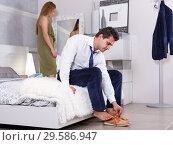 Купить «Man sitting on bed and dressing», фото № 29586947, снято 24 сентября 2018 г. (c) Яков Филимонов / Фотобанк Лори